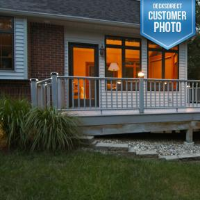 Aries Solar Post Cap Light by Aurora Deck Lighting in Bronze on a white railing combined with Low Voltage LED Lights