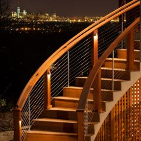 Feeney CableRail standard assemblies and intermediate pickets installed with custom curved wood stair railing.