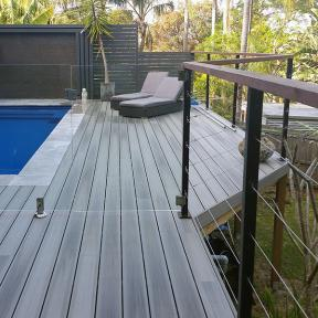 Water damage and rot resistant, DuraLife Siesta Grooved Edge Deck Boards, shown in Garapa Gray, beautifully frame a pool area.