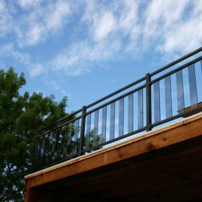 Fortress Pure View Glass Railing system in Gloss Black with Glass Balusters in Smoke. Also features Fortress FE26 Square Handrail sections used as a decorative third rail.