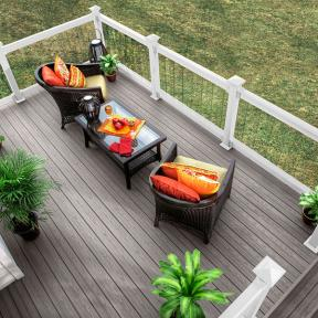 The stunning looks of bright patio furniture against the dark shades of Genovations PVC decking, shown in Driftwood, creates a unique image.
