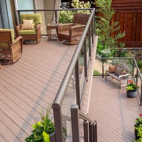 A low-profile way to highlight your chic looking bronze railing, Genovations deck flooring in Sandalwood, makes an organic looking space.