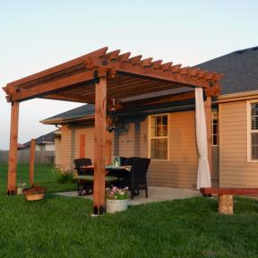 Patio Pergola featuring the Post Base Kit, Post to Beam Bracket Kit, and Rafter Clips by OZCO Ornamental Wood Ties