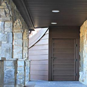 Trex RainEscape installed in a breezeway finished off with brown beadboard and lighting