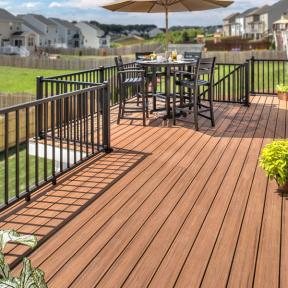 Gain a new outdoor dining room with stain-resistant Trex Transcend in Tiki Torch and furniture matching Trex Signature railing in Charcoal Black.
