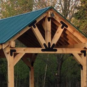 Creek Pavilion featuring the Truss Base Fan, Truss Accents, Laredo Sunset Truss Tie Plate, Outside Flush Tie Plate, and Laredo Sunset Flush Inside Tie Plate by OZCO Ornamental Wood Ties