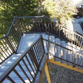 Westbury Tuscany Series Aluminum Stair Railing in Bronze Fine Texture. Also features Westbury Stair Crossover Brackets, Post Skirts and Post Caps.