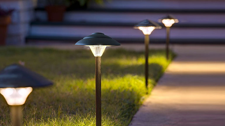 A well-lit pathway featuring the Stepped Mushroom Pathway Light by Dekor.