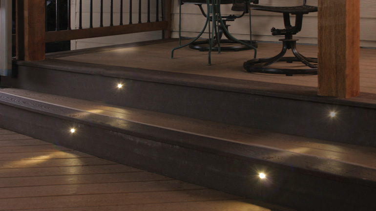 Millennium recessed LED deck lights from Dekor are installed in stair risers to illuminate the tread below for increased visibility