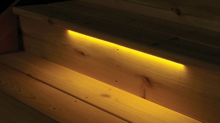 An 18 inch Odyssey Strip Light from Aurora Deck Lighting is installed underneath the tread of a cedar stair tread, illuminating the step below with warm LED light for safety and ambiance
