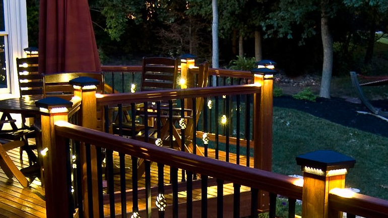 Dusk on a backyard deck is illuminated by several Dekor Lit Post Caps, shown in Antique Metal Black Finish