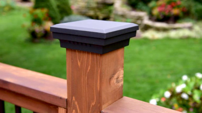 A lushly-landscaped backyard is viewed from a wood deck with wood railing topped with Premium Cast Flat Top Post Caps by Dekor in Antique Metal Black finish