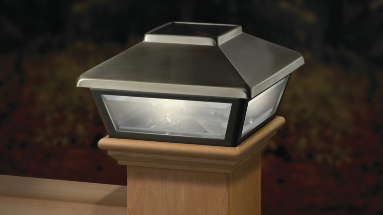 The Low Profile Solar Post Cap Light by Deckorators is installed on a cedar deck post and provides gentle illumination