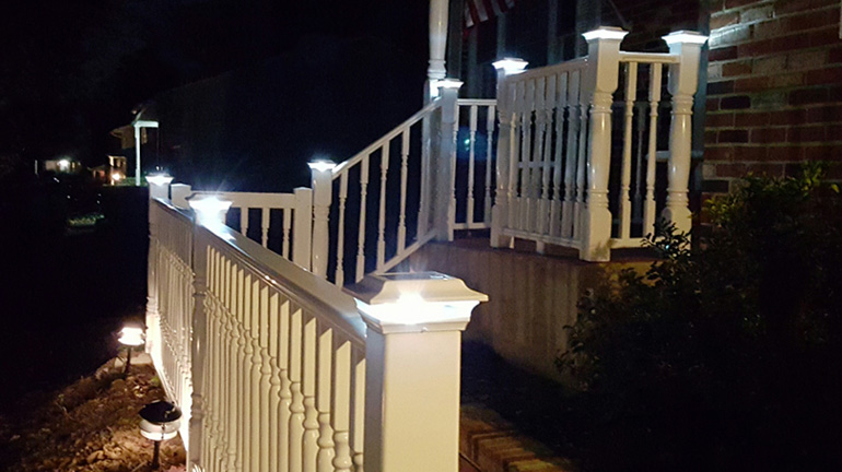 A decorative vinyl front porch railing with colonial-sytle balusters is highlighted with white aluminum solar post cap lights and Solar Deck Lighting from Classy Caps