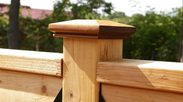 The Tucson style IPE Post Cap by Acorn Deck Products is installed on a cedar deck post