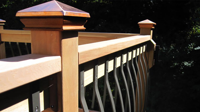 A wood deck featuring metal top wood post caps and bow balusters