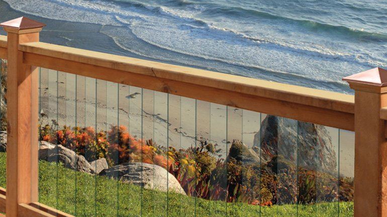 A seaside deck railing includes cedar posts and rails, Glass Deckorators Balusters, and Victoria High Point post caps with cedar bases and copper tops