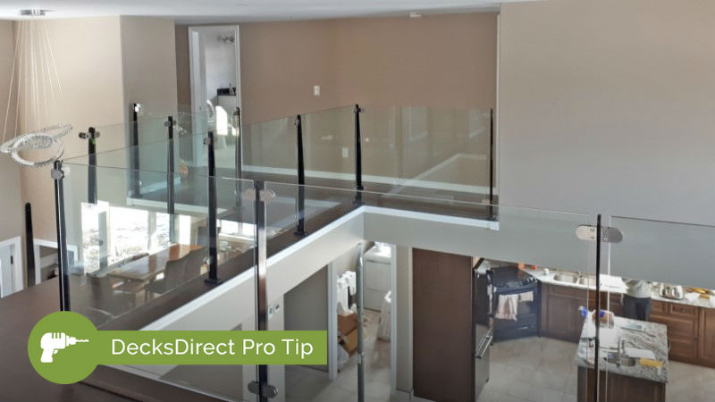 Sleek and modern InvisiRail glass railing panels installed inside the home on an upper level