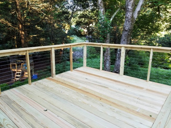 Pressure-treated lumber is a low-cost deck frame material that provides a long-lasting outdoor space